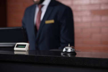 hotel reception desk with bell and blurred receptionist on background