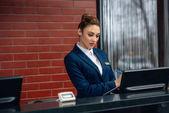 Junge Hotelrezeptionistin nutzt Computer am Arbeitsplatz