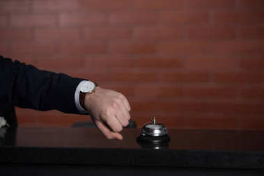 cropped shot of businessman looking at watch while waiting for service at hotel reception desk