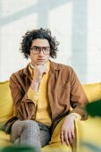 Photo Male fashion model with eyeglasses holding hand on chin