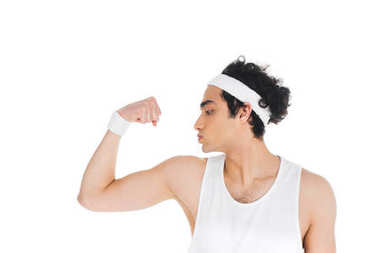 Side view of young thin sportsman showing muscles on hand isolated on white
