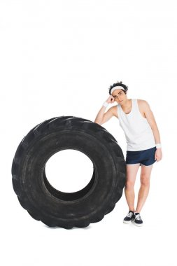 Thin sportsman standing beside tire of wheel isolated on white