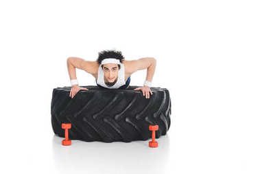 Young thin sportsman doing push ups on tire of wheel isolated on white