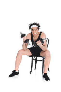 Young skinny sportsman exercising with dumbbells while sitting on chair isolated on white