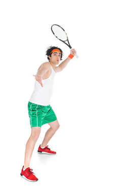 Thin sportsman in headband standing with racket isolated on white