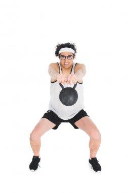Skinny sportsman in eyeglasses holding kettlebell in hands isolated on white
