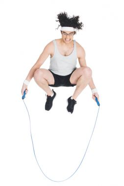 Skinny sportsman doing jump rope workout isolated on white