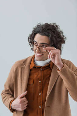 Smiling stylsih man looking over eyeglasses isolated on grey