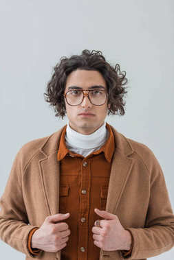Portrait of young stylish man in eyeglasses isolated on grey