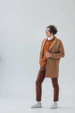Male fashion model in eyeglasses wearing coat isolated on grey