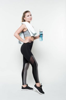 Blonde woman in sport clothes with towel on shoulder holding water bottle isolated on white