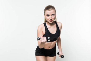 Smiling fitness woman with ponytail lifting dumbbells isolated on white
