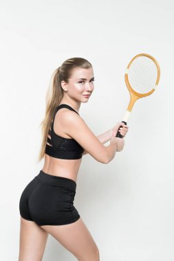 Smiling fitness woman holding tennis racket isolated on white