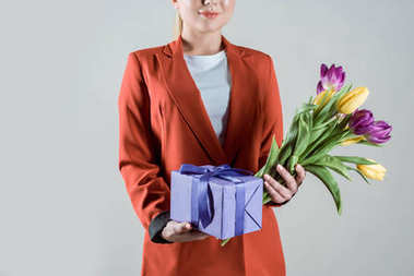 Gift box and tulips bouquet in hands of stylish woman isolated on grey