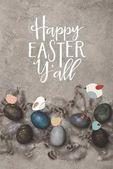 pohled shora malovaná velikonoční vajíčka s peřím na betonu povrch s ptáky a Veselé Velikonoce a nápisy