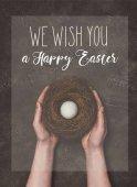 Nézd, az ember, aki fehér tojásos fészket vágott, és kívánunk Boldog húsvéti betűkkel