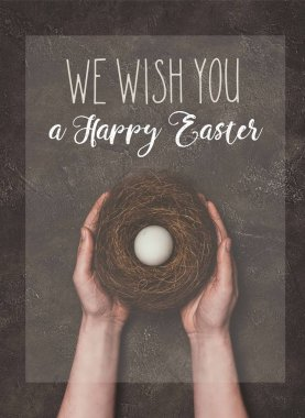 cropped view of man holding nest with white egg, and We wish you a Happy Easter lettering