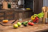 Fényképek friss bio zöldségek és gyümölcsök a fa konyhaasztal