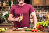 Fotografie cropped shot of smiling young man holding glass of fresh orange juice at kitchen
