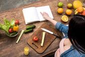 Oříznout záběr těhotná žena čte kuchařka při vaření v kuchyni
