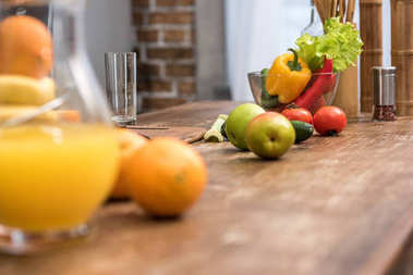selective focus of orange juice in glass jug, fresh fruits and vegetables on kitchen table
