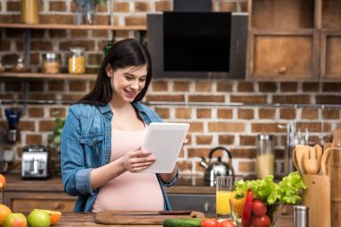 smiling young pregnant woman using digital tablet while cooking at kitchen
