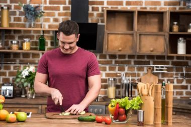 smiling young man cutting celery while cooking salad in kitchen
