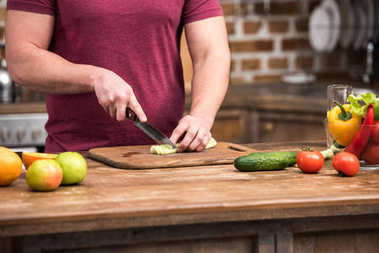 cropped shot of young man cutting celery while cooking salad in kitchen