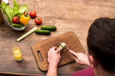 selective focus of man cutting celery on wooden chopping board