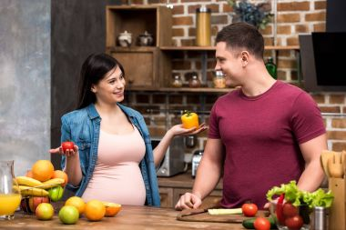 happy young pregnant couple smiling each other while cooking together at kitchen