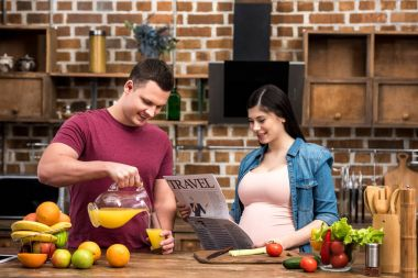 smiling young man pouring orange juice and happy pregnant woman reading travel newspaper