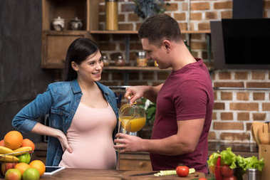 smiling young man pouring fresh orange juice to pregnant wife