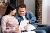 Fotografie happy young pregnant couple using digital tablet together at home