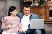 Fényképek boldog, fiatal terhes pár hitelkártyát használ laptop otthon együtt