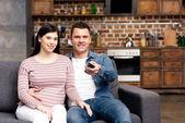 Fényképek boldog, fiatal terhes pár használ távoli ellenőr és tv-nézés együtt otthon