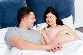 Mladá těhotná snoubence leží vedle sebe v posteli a při pohledu na sebe
