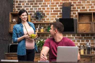 smiling young man using laptop and looking at pregnant wife holding glass bowl with vegetable salad