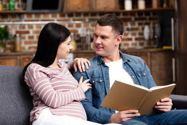 happy young pregnant woman looking at smiling husband reading book at home