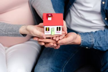 close-up partial view of young pregnant couple holding small house model