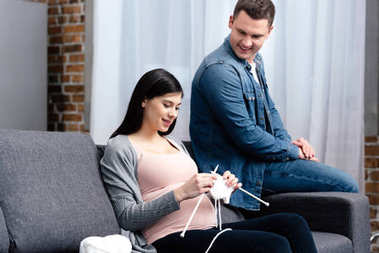 smiling young man looking at pregnant wife knitting on sofa
