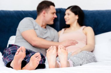 happy young pregnant couple smiling each other on bed