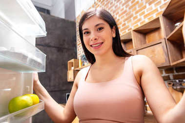 smiling young pregnant woman looking into refrigerator
