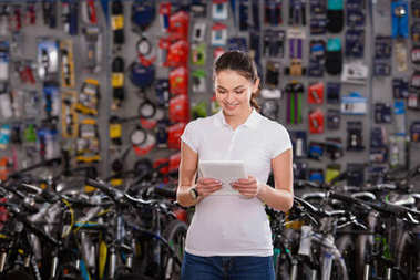 smiling young woman using digital tablet while working in bicycle shop