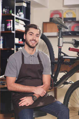 handsome young repairman in apron smiling at camera in workshop