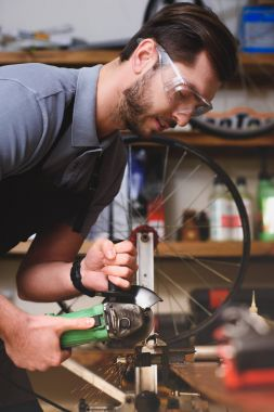 young man in protective goggles holding angle grinder in workshop