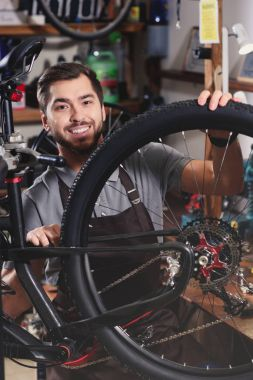handsome young man in apron fixing bicycle and smiling at camera in workshop