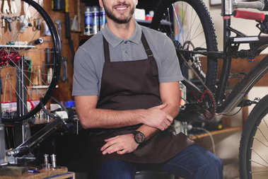 cropped shot of smiling young man in aron sitting near bicycles in workshop