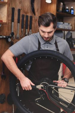 young man in apron fixing bicycle wheel and chain with wrench in workshop