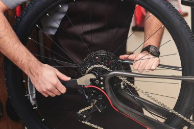 cropped shot of man in apron fixing bicycle wheel and chain with wrench