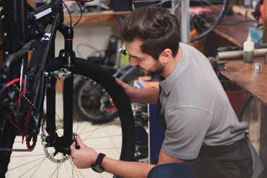 handsome young mechanic in apron fixing bicycle wheel in workshop
